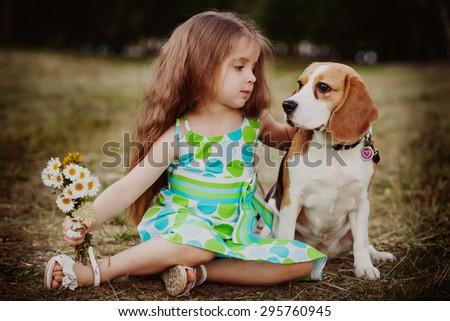 little girl hugs her dog outdoors - stock photo