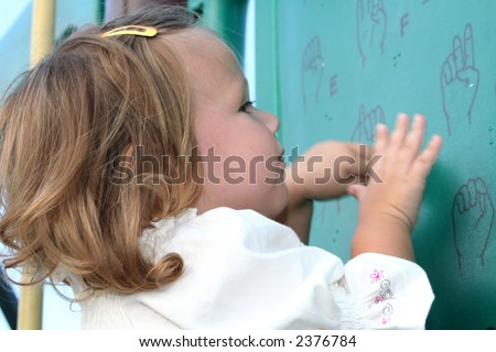 Little girl imitating sign language symbols printed on a board at a playground.