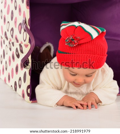 Little girl in a basket with christmas hat. - stock photo