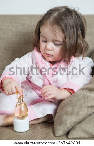 little girl in a bathrobe on the couch with body cream
