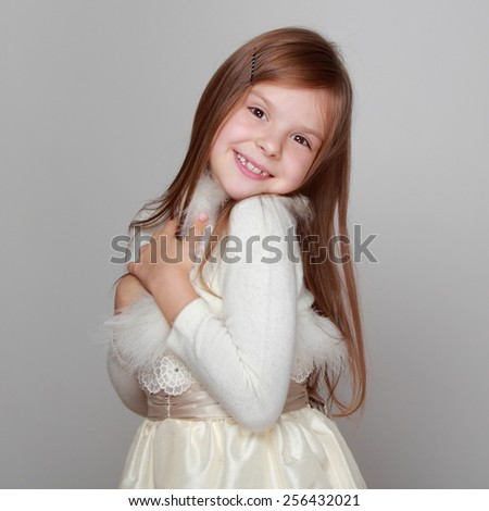 little girl in a beautiful dress is dancing and having fun on a gray background - stock photo