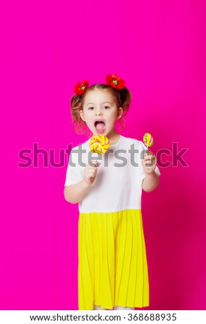 Little girl in a beautiful dress with a big candy lollipop in hands - stock photo