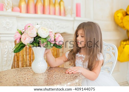Little girl in a beautiful white dress looking at bouquet of flowers.