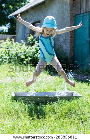 Little girl in a blue bathing suit having fun jumping in the tub full of water in the yard in the village - stock photo