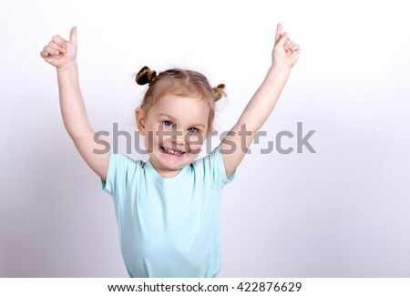 little girl in a blue t-shirt raised her hands up and smiling, blonde