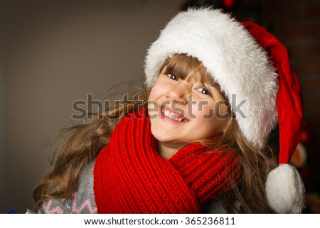 little girl in a cap of Santa Claus in a red scarf and knit sweater against the backdrop of the Christmas tree, dark background - stock photo