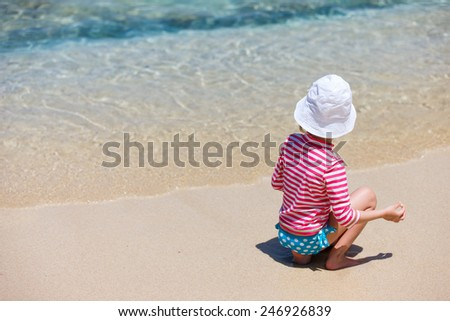 Little girl in a colorful sun protection swimwear on vacation at tropical beach - stock photo