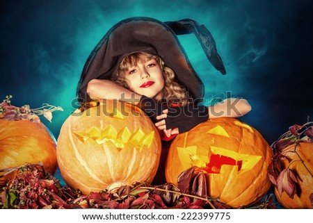 Little girl in a costume of witch posing with pumpkins over dark background. - stock photo