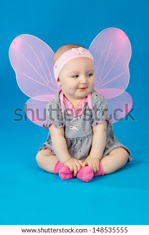 little girl in a dress and wings on a blue background