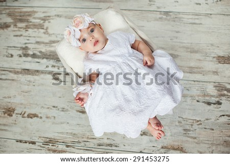 Little girl in a dress lying in a basket on the wooden floor. Beautiful baby with big eyes. - stock photo