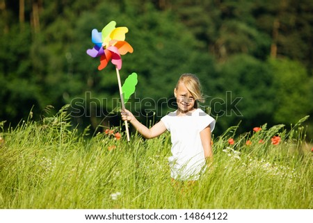 Little girl in a field playing with a colorful windmill toy - stock photo