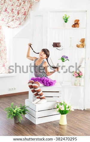 little girl in a fluffy skirt and striped stockings. Hairstyle of the two braids. - stock photo