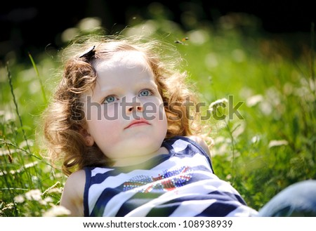 Little girl in a green field. Focus on her face - stock photo