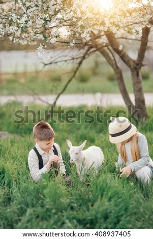 little girl in a hat with a boy playing with a little white goat in lush garden - stock photo