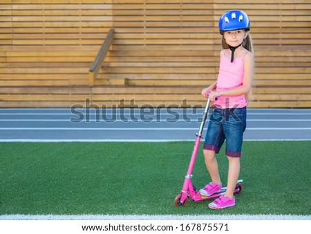 Little girl in a helmet with scooter on a green grass on stadium