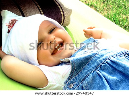 Little girl in a kerchief, lying on the deck-chair in the garden. - stock photo