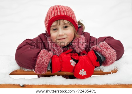 Little girl in a knitted hat leaned on the bench - stock photo