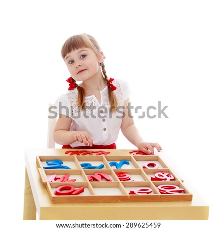 Little girl in a Montessori kindergarten is studying the letters - isolated on white background - stock photo