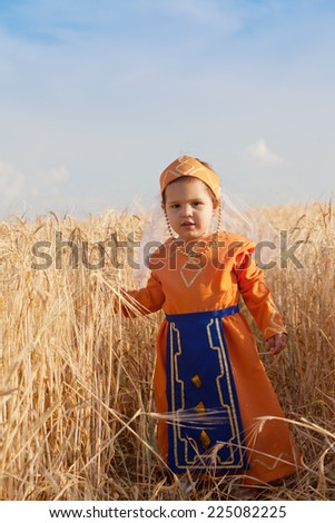 Little girl in a national Armenian dress costs among wheat field - stock photo