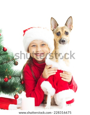 little girl in a New Year's suit hugging his dog on a white background  - stock photo
