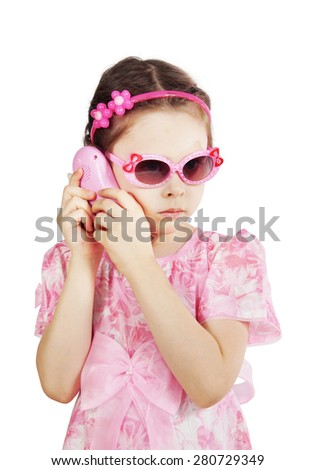 Little girl in a pink dress talking on the toy phone - stock photo
