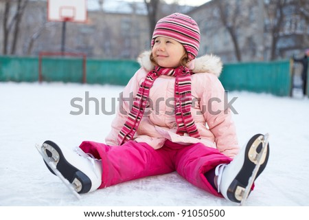 little girl in a pink jacket, sitting on the ice with skates on his feet after the fall - stock photo