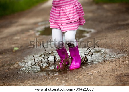 Little girl in a puddle - stock photo
