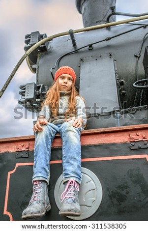 Little girl in a red cap on a background of the railway locomotive. - stock photo