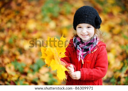 Little girl in a red coat at autumn holding leaves - stock photo