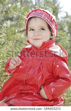 Little girl in a red coat sitting in spring forest on grass.