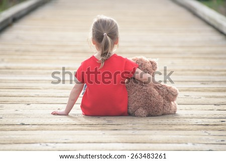 Little girl in a red dress waiting on a boardwalk hugging teddy bear, view from behind - stock photo
