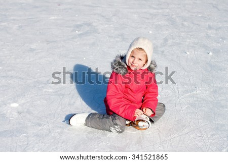little girl in a red jacket, sitting on the ice with skates on his feet after the fall - stock photo