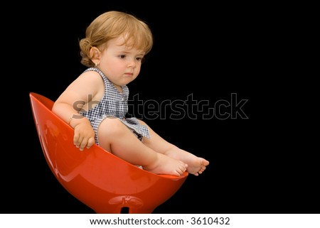 Little girl in a red plastic swivel chair - thinking - isolated on black - copy space - stock photo