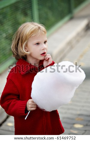 Little girl in a red sweater holding a cotton candy