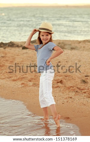 Little girl in a summer dress is played on the Black Sea coast at sunset - stock photo