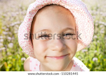 Little girl in a summer panama playful smile - stock photo