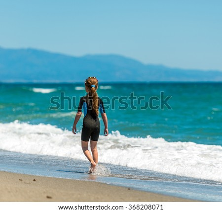 little girl in a wetsuit walking  along the beach. back view
