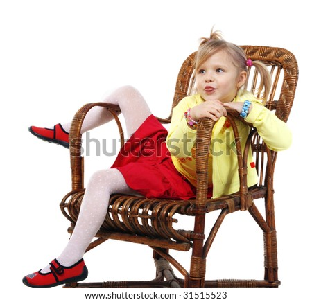 Little girl in a wicker chair on a grey background