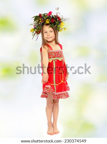 Little girl in a wreath and a red dress. - stock photo