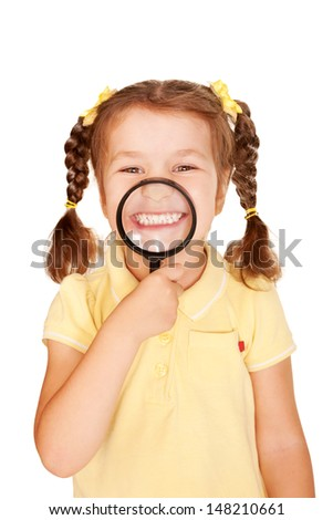 Little girl in a yellow T-shirt smiling through a magnifying glass. Isolated on white background - stock photo