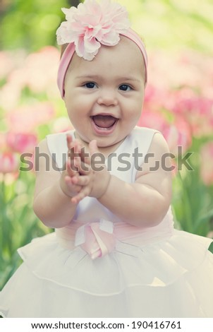 little girl in an elegant dress to stand near blossoming tulips - stock photo