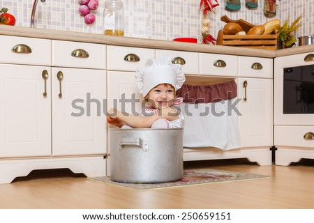 Little girl in apron and cap of the cook sitting  in the kitchen in the house. Mother's helper. 2 year old. - stock photo