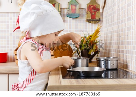 Little girl in apron and cap of the cook stands in the kitchen near cooker in the house. Mother's helper. 2 year old. - stock photo