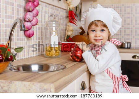 Little girl in apron and cap of the cook with an apple stands in the kitchen near sink at home. Mother's helper. 2 year old. - stock photo