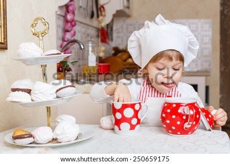 Little girl in apron and cap of the cook with sweet desserts sits at the dining table in the kitchen in the house. Mother's helper. 2 year old. - stock photo
