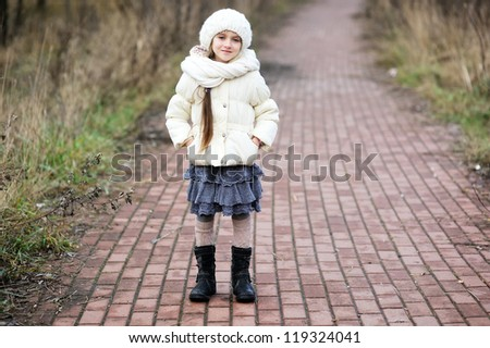 Little girl in autumn outfit standing on park road - stock photo