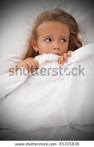 Little girl in bed awaken by nightmares laying scared - stock photo