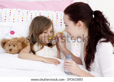Little girl in bed taking syrup with her mother - stock photo