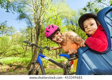 Little girl in bike seat behind her sporty mother