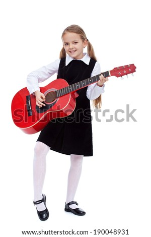 Little girl in black dress holding red guitar, learning to play it - isolated - stock photo